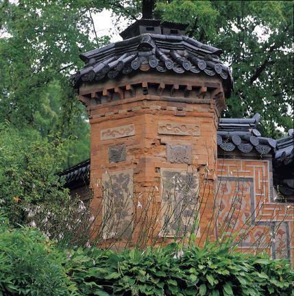 덩쿨무늬, 나비무늬, 학, 소나무, 국화가 보이는 굴뚝 벽과 꽃담